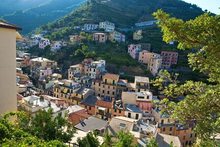 cinque: a view looking down to the old village of riomaggiore and the surounding hillside, located in cinque terra, italy.