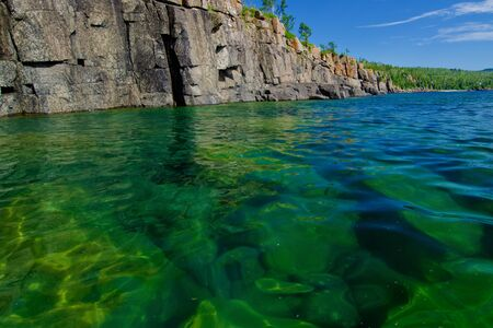 rise above: cliffs rise above submerged boulders, in lake superior, at split rock state park, minnesota. Stock Photo
