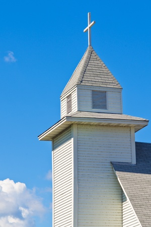 a small white church steeple and cross, in rural minnesota. Stock Photo