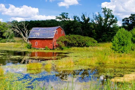 a crumbling old weathered barn, reflecting from the edge of a pond, in rural minnesota.