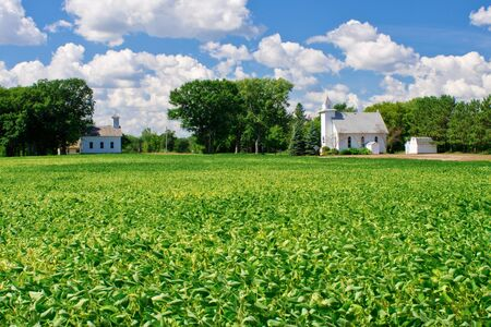 rural community: a small schoolhouse, white church and farmland, in rural minnesota. Stock Photo