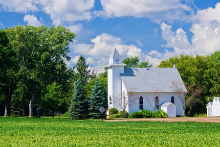 rural community: a small white church and farmland, in rural minnesota.