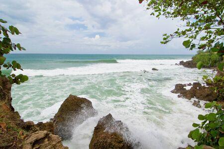 crashing waves pound against the boulder strewn rincon shoreline, puerto rico.