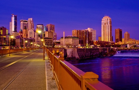 a view of the minneapolis skyline and the mississippi river at dawn, as seen from the stone arch bridge.
