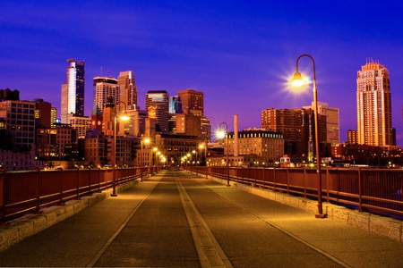 the the early morning light rises on the minneapolis skyline, as seen from the stone arch bridge.