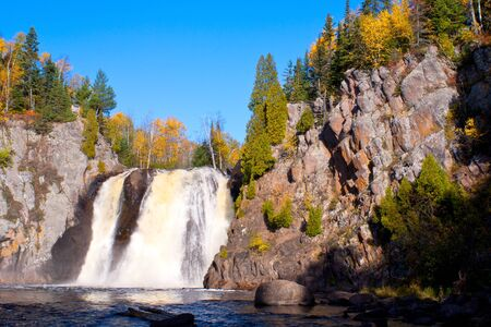 the morning sun rises on baptism falls in autumn, tettegouche state park, minnesota.
