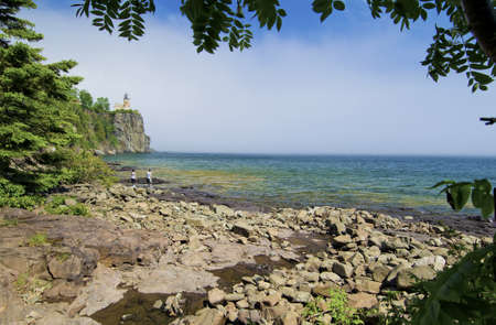 superiors: a couple looks out to the split rock lighthouse, on lake superiors north shore, minnesota. Stock Photo