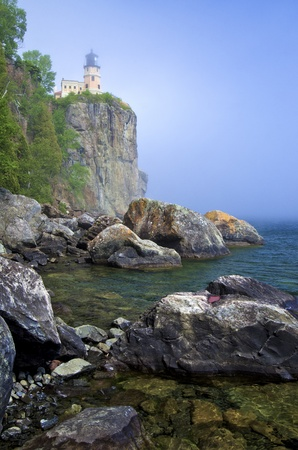 split rock lighthouse, rises above the boulder strewn, foggy shoreline, of lake superior, minnesota. Banco de Imagens