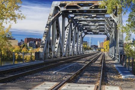a railroad bridge spans over the mississippi river, autumn, minneapolis, minnesota.