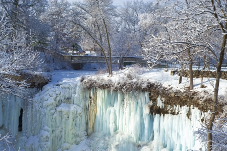 a frozen minnehaha falls and footbridge in winter, minneapolis, minnesota