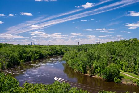 mississippi river: a boat travels along a bend on the mississppi river toward downtown minneapolis, minnesota