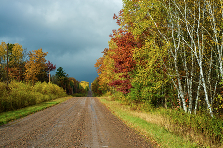 onward: an autumn rain moves onward and sunshine returns to a wet country road in central wisconsin   Stock Photo