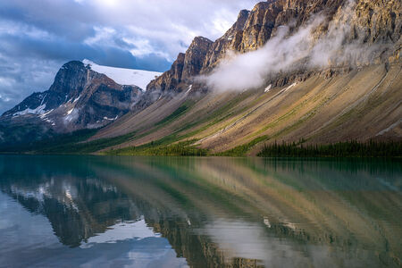 reflects: a clearing storm reflects off of bow lake, banff national park, alberta canada