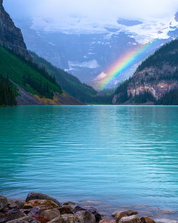 louise: a rainbow glows at the end of lake louise, banff national park, alberta canada