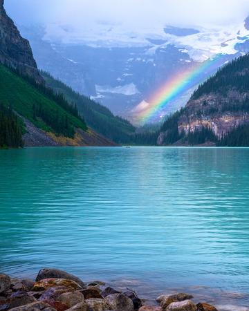 the end of a rainbow: un arco iris brilla al final de Lake Louise, Parque Nacional Banff, Alberta Canad�