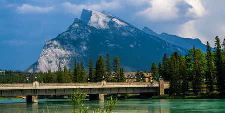 banff: mount rundle rises over the bow river and the banff avenue bridge, banff national park, canada.