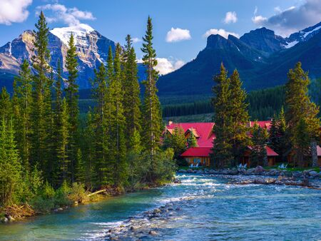 the pipestone river rushes past log cabins in lake louise village, banff national park, alberta, canada.