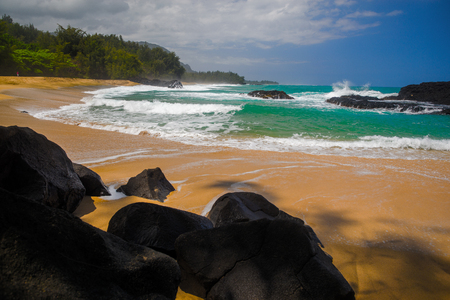 thundering: black lava rocks, golden sands, aquamarine waters, and a green lush shoreline, make lumahai beach, on kauais north shore, one of the most beautiful in all of the hawaiin islands. Stock Photo