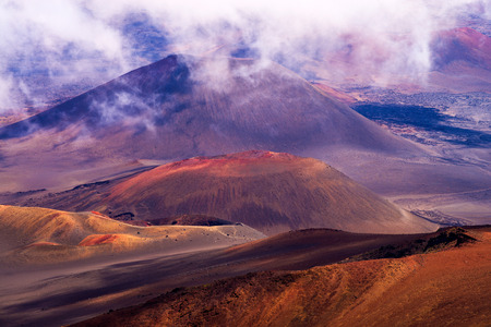 high up in the clouds of maui, haleakala crater, shows an otherworldly landscape of reds, oranges, browns and gray volcanic rock. haleakala national park.
