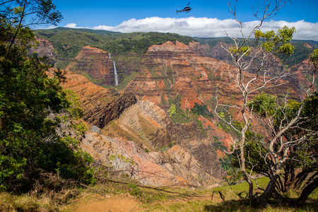 waimea canyon state park: a helicopter hovers over the grand canyon of the pacific, waimea canyon, with waimea falls in the background.