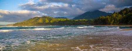 paradise bay: morning seafoam and a view looking easward on kauais north shore, at wainiha beach, kauai, hawaii.