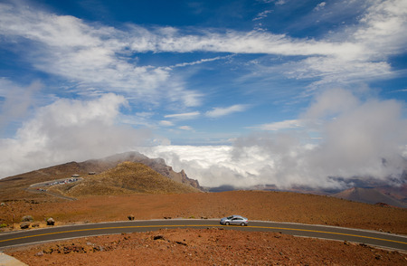 otherworldly: the road to the summit of haleakala, twists and turns high above the clouds of maui, and haleakala crater, haleakala national park, maui, hawaii.