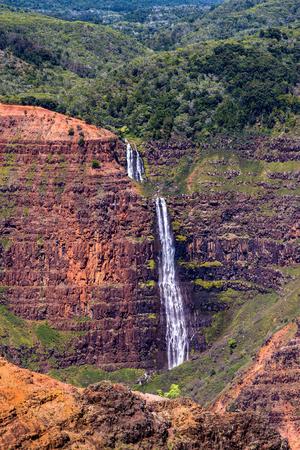 waimea canyon state park: waimea falls cascades down into waimea canyon, on the garden island of kauai, hawaii.