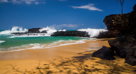 thrill seekers waiting to cling to lava rocks, when large winter waves break over them, creating cascading waterfalls, pocketing the seekers inside, on kauais north shore. Stock Photo