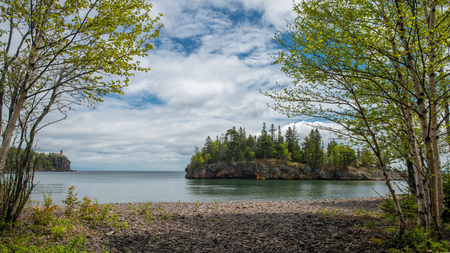 birch grow on the rocky shoreline of lake superior, ellingson island and split rock lighthouse beyond, minnesota.