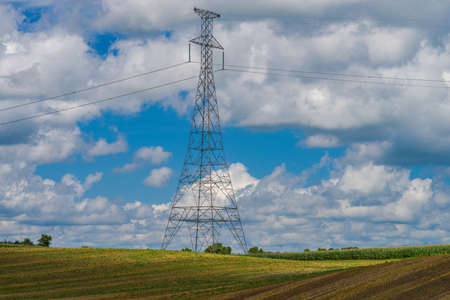 a power line tower rises high above farmland in central minnesota Stock Photo