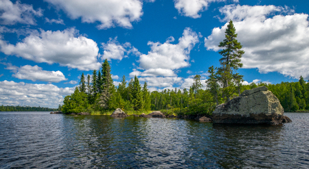 a rocky shoreline and pine studded forests, await any paddler heading up along the eastern side of sawbill lake, in the boundary waters canoe area wilderness, minnesota. 版權商用圖片