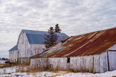 a weathered shed and barn, slowly gives way to the elements of time, winter, wisconsin Stock Photo