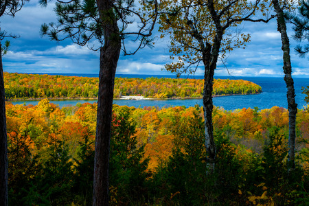 on an overlook, looking out onto lake michigan, and an autumn colored island, peninsula state park, wisconsin.