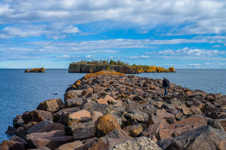 a backpacker hikes out toward pellet island, on lake superiors north shore, silver bay, minnesota.