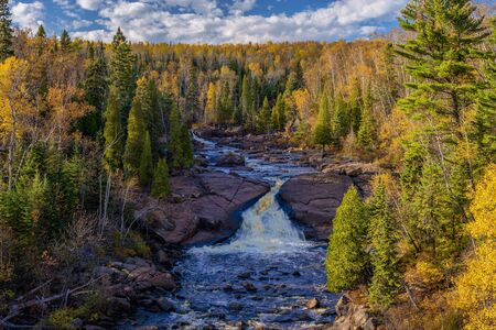 the beaver river carves its way through a boreal forest, droping down into a waterfall, before entering the north shore of lake superior, beaver bay, minnesota.
