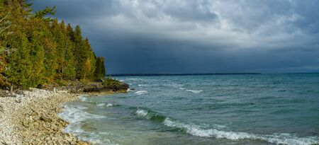 stormy skies beyond a rocky outcropping in autumn, at cave point county park, door county, wisconsin