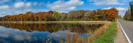 a panoramic view of an autumn lake and roadway, in rural washington county, minnesota. Фото со стока