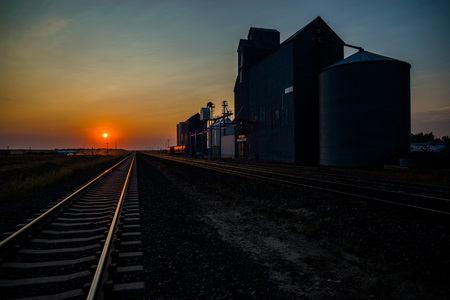 the morning sun rises over golden railroad tracks, next to the hingham grain elevator, in northern montana.