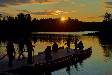a group of canoers preparing to go canoeing on the dock at sawbill lake, near the entrance of the bwcaw, northern minnesota, sunset.