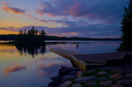 a canoer paddles out onto sawbill lake, to join other canoers, northern minnesota.
