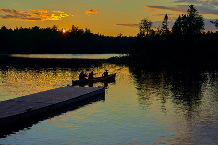 canoers setting out on sawbill lake at sunset, near the entrance of the bwcaw, in northern minnesota.
