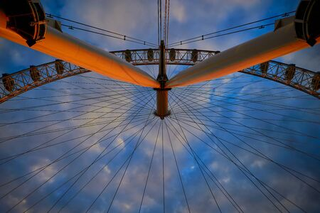 the london eye glows at sunset, in contrast against darkening clouds and blue sky, london, england.