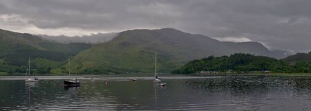 a panoramic view of the glencoe marina on loch leven, surrounded by the beautiful mountains of the scotish highlands, glencoe, scotland. Banco de Imagens