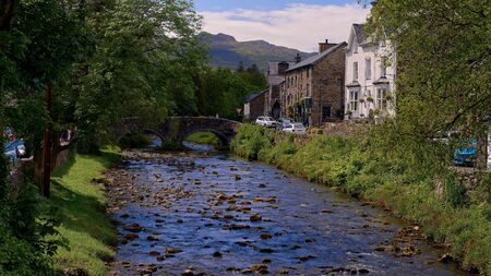 a small stone arch bridge, arches over the river colwyn in beddgelert, wales