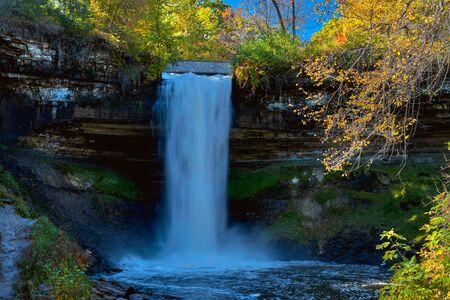 minnehaha falls drops 53 feet down into a limestone amphitheater, surrounded by autumn foliage, minneapolis, minnesota.