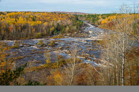 the saint louis river tumbles downward through a boreal forest in autumn, in jay cooke state park., minnesota.
