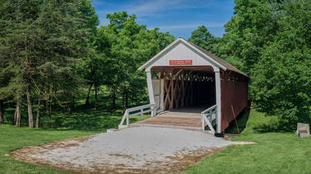 built in 1870, the historic cuttler-donahoe covered bridge, crosses over a small creek, in middle river park, winterset, iowa.