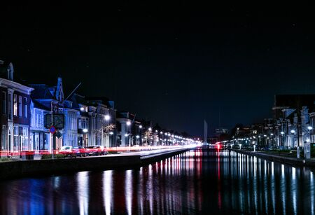 streetlife: Cars are chasing their lights along a typical Dutch canal in the city of Assen in the Netherlands. City streetlife by night.