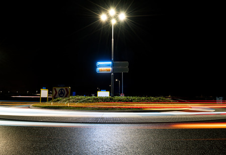 assen: A dark roundabout at night near the TT circuit in Assen, the Netherlands. Passing cars create beautiful light trails.
