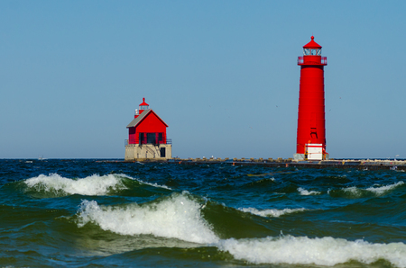 Waves on Lake Michigan roll past the lighthouse and pier in Grand Haven, Michigan. The red lighthouse is contrasted against a blue sky and water.